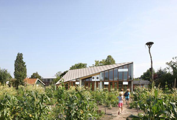 Alle basisscholen in Amsterdam hebben een speciaal onderwijsprogramma over natuur en milieu. In dit lesprogramma onderhoudt ieder kind gedurende een half jaar een eigen schooltuintje en krijgt het aanvullend les in een speciaal hiervoor gemaakt natuur- en milieu educatiecentrum (NME). Het nieuwe NME in Amsterdam-Noord vervangt twee noodlokalen die gedurende 5 jaar op dezelfde locatie stonden. Het gebouw is uniek, omdat het zelf fungeert als lesmateriaal: alle (energetische) duurzaamheidsmaatregelen zijn zichtbaar en beleefbaar. Zo komt de bijzondere vorm van het dak door een optimale orientatie op de zon. En de grote betonnen platen met glas ervoor (de Trombe-wanden) verwarmen frisse lucht voordat die de klaslokalen instroomt.